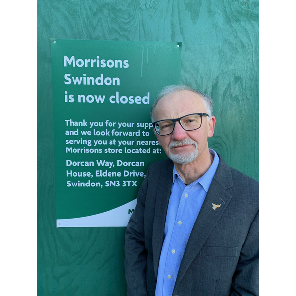 Councillor Stan Pajak standing next to the Morrisons closure sign
